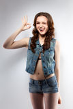 Image of cheerful young girl shows gesture OK. On gray background Royalty Free Stock Images