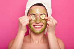 Image of cheerful young woman has green mask on face, applies slices of cucumber on eyes, smiles happily, wears white towel on stock photography