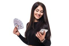 Image of cheerful young woman standing isolated over white background looking camera holding money using mobile phone. Image of cheerful young woman standing Stock Image
