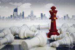 Chess king with China flag defeating white chess. Image of a chess king with China flag defeating white chess pieces. Shot with modern city Stock Photography