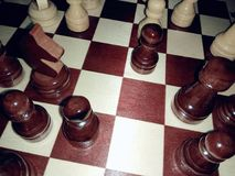 An image of a chessboard with black and white figures in a projection with a flash.  Royalty Free Stock Photos