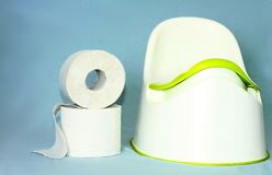 Child`s toilet potty with toilet paper. Image of child`s toilet potty with toilet paper representing potty training stock photography
