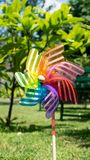 Image of childish colorful pinwheel on the outside. Garden with green grass in a sunny summer day. Rainbow flag LGBT Happy colors. In small windmill, toy stock images