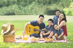 Chinese family playing a guitar in the park. Image of Chinese family enjoying holiday while picnicking and playing a guitar together in the park royalty free stock images