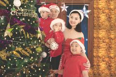 Chinese family decorating Christmas tree at home. Image of Chinese family smiling at the camera while decorating Christmas tree together at home Royalty Free Stock Photography