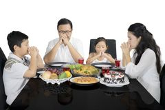 Christian family praying before having lunch. Image of Christian family praying before having lunch, isolated on white background Royalty Free Stock Photos