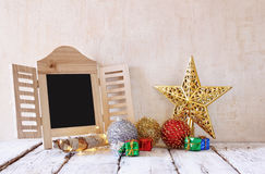 Image of christmas decorations and chalkboard in front of white wooden background Stock Images