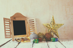 Image of christmas decorations and chalkboard in front of white wooden background Stock Photos