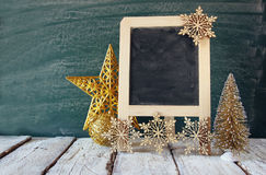 Image of christmas decorations and chalkboard in front of white wooden background Stock Photography