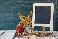 Image of christmas decorations and chalkboard next to blackboard background Royalty Free Stock Images