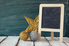 Image of christmas decorations and chalkboard next to blackboard background Royalty Free Stock Photo