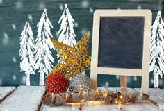 Image of christmas decorations and chalkboard next to blackboard background with winter concept drawings Stock Photo