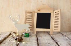 Image of christmas decorations, chalkboard and white raindeer in front of white wooden background. faded retro style image Stock Image