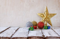 Image of christmas decorations in front of white wooden background Royalty Free Stock Image
