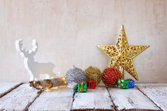 Image of christmas decorations and white raindeer in front of white wooden background Royalty Free Stock Photo