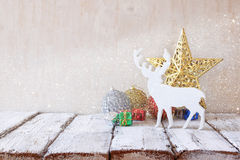 Image of christmas decorations and white raindeer in front of white wooden background Stock Photography