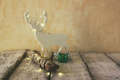 Image of christmas decorations and white raindeer in front of white wooden background Stock Images