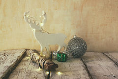Image of christmas decorations and white raindeer in front of white wooden background Royalty Free Stock Photos
