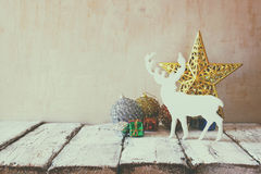 Image of christmas decorations and white raindeer in front of white wooden background Stock Image