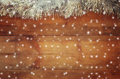 Image of christmas festive decoration on wooden background. retro filtered with abstract snowflakes overlay Stock Photos