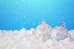 Image of christmas festive tree white ball decoration in front of blue background background. Glitter overlay. Image of christmas festive tree white ball royalty free stock image