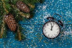 Image of Christmas branches of spruce, cones and clocks, snow royalty free stock photos