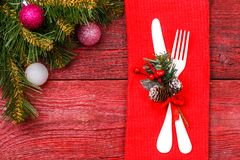 Image of Christmas table with fork and knife on red napkin,. Spruce branches, festive balls Royalty Free Stock Photography