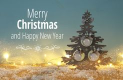 Image of christmas tree with ball decorations on snowy wooden table. Royalty Free Stock Images