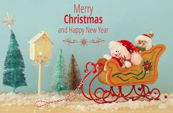 Image of christmas tree and snowmen on the wooden old sled over snowy wooden table. Image of christmas tree and snowmen on the wooden old sled over snowy wooden Royalty Free Stock Images