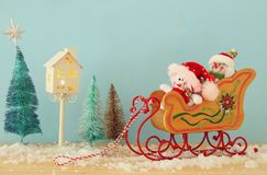 Image of christmas tree and snowmen on the wooden old sled over snowy wooden table. Image of christmas tree and snowmen on the wooden old sled over snowy wooden Stock Images