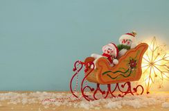 Image of christmas tree and snowmen on the wooden old sled over snowy wooden table. Image of christmas tree and snowmen on the wooden old sled over snowy wooden Stock Photo