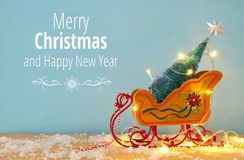 Image of christmas tree on the wooden old sled over snowy wooden table Royalty Free Stock Images