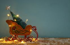 Image of christmas tree on the wooden old sled over snowy wooden table Royalty Free Stock Image