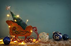 Image of christmas tree on the wooden old sled over snowy wooden table. Royalty Free Stock Image