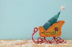 Image of christmas tree on the wooden old sled over snowy wooden table. Stock Photography