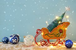 Image of christmas tree on the wooden old sled over snowy wooden table. Stock Image
