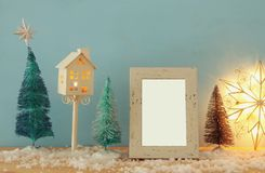 Image of christmas trees next to empty photo frame on snowy wooden table. For photography montage. Image of christmas trees next to empty photo frame on snowy royalty free stock photos