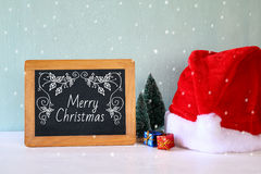 Image of christmas trees and santa hat next to blackboard Royalty Free Stock Image