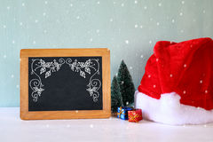 Image of christmas trees and santa hat next to blackboard. Stock Photography