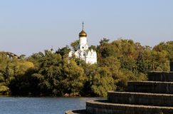 The image of the church in the trees on the banks of the Dnieper River