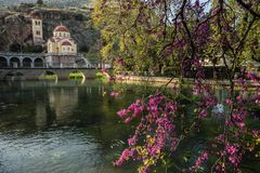 Church under the rock, river and flowers near Kefalary on Peloponnese in Greece. Image of church under the rock, river and flowers near Kefalary on Peloponnese stock photos