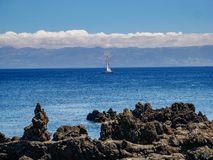 Image from a cliff with a sailing boat in the atlantic and the island of Pico with mountain Pico in the background stock images