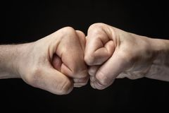 Concept of confrontation, competition etc. Image close up clash of two fists on black background. Concept of confrontation, competition etc royalty free stock photography