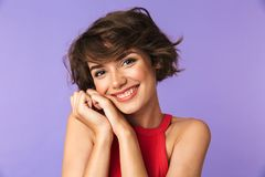 Image closeup of caucasian satisfied girl 20s in casual wear smiling and holding hands at face, isolated over violet background. Image closeup of caucasian stock photos