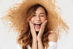 Image closeup of excited woman 20s wearing big straw hat screaming and holding hands at face, isolated over white background royalty free stock photos