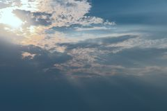 The image of clouds in the blue sky. The sun shines through the clouds. stock photo