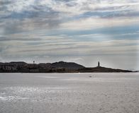 Image of the coast and sky line of La Coruna Spain with the to. Wer of Hercules standing out in the right half and cloudy sky with sunbeams reflected in the Royalty Free Stock Photography