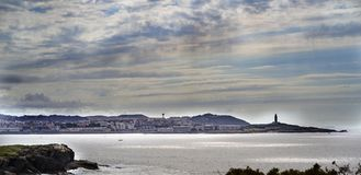 Image of the coast and sky line of La Coruna Spain with the to. Wer of Hercules standing out in the right half and cloudy sky with sunbeams reflected in the Stock Photos