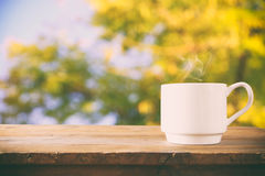 Image of coffee cup over wooden table and tree leaves.  Royalty Free Stock Photo