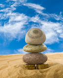 Image of coins and stones on the sand close up Stock Images